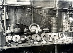 View of an exhibition stall inside an open structure housing an exhibition of local produce. Produce on display on stall include: Ibo carvings, Nupe brasswork, Ibo ankle-ornaments, Ibo combs, Ibo [?] mats, two swords from Benin, a lower Niger brass or bronze hip mask in the form of a face, a musical instrument. Medium: Gelatin silver print.