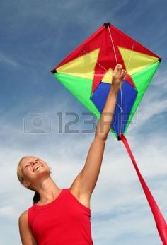Happy Young Woman Flying a Kite Stock Photo