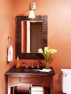 Warm wood tones paired with rich russet walls create a dramatic look in any small space, such as this bathroom