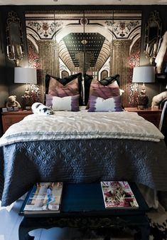 Eclectic bedroom with folding screen headboard, blue quilt, white silk quilt, black Chinese table, matching wood nightstands, purple pillows and vintage mirrors.