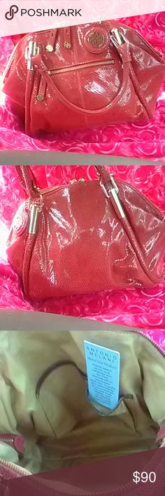 Authentic Antonio Melani Gorgeous red 100% leatherAntonio Melani handbag brand new! Gold hardware with Antonio's signature stamp engraved on all the hardware,produced with the finest materials with unsurpassed quality and  craftsmanship! Front pocket,2 way top zipper,2 zip pockets in,with 3 slot pockets for cell, ect... large dust bag included and directions on how to care for this incredible handbag!  Never been out of the house ,slight spot of piling from storing! Not noticeable! Price…