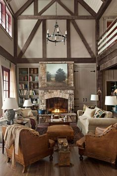In this Georgia lake house, appealingly asymmetrical built-ins—one with hidden storage, the other open—flank the great room's fieldstone fireplace. French leather club chairs from Wyatt Childs, plus a pair of Mitchell Gold + Bob Williams sofas, serve up plenty of seating.