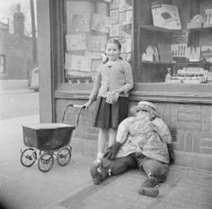 Nigel Henderson 'Photograph of an unidentified girl outside a shop with a toy pram and a stuffed figure', © Nigel Henderson Estate