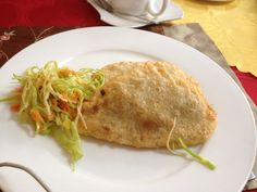 Mongolian food - khuushuur. Khuushuur is very popular in Mongolia. This fried dough filled with minced mutton, salt and onions is cheap and easy to eat. Sometimes it is served with salad (cabbage) on the side.