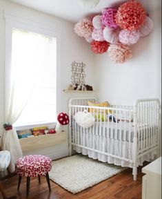 tissue paper pom pom decoration above crib - in a mix of teal, white, blue?