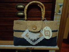 Bolso de rafia con aplicación de algodón y asas de madera.