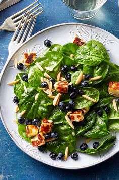 The combination of sweet berries, crunchy almonds and salty cheese in this spinach salad really can't be beaten. Pan-fried bites of the Greek cheese halloumi are a delicious stand-in for croutons. #salads #saladrecipes #healthysalads #saladideas #healthyrecipes