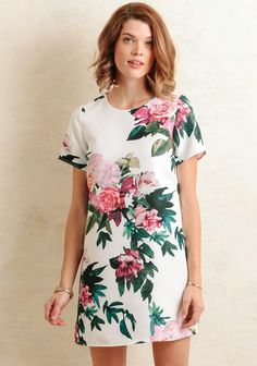 Feminine and chic, this white shift dress is adorned with an oversized floral print in vibrant hues of magenta, green, and teal. Designed with a pebbled texture and short sleeves, this lovely dre...
