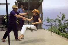 """Jackie getting help off the swing in Skorpios. Onassis once said, """"I spend millions on her clothing, but all she seems to wear is white pants and black t-shirts!"""" Yes, Ari, she did and created an iconic look that endures and compliments to this day!"""