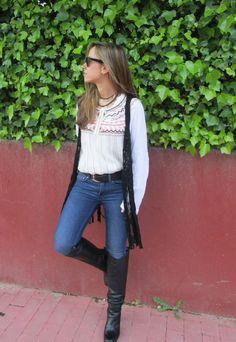 Comprar ropa de este look:  https://lookastic.es/moda-mujer/looks/chaleco-blusa-campesina-vaqueros-botas-de-cana-alta-correa/2098  — Vaqueros Azules  — Botas de Caña Alta de Cuero Negras  — Correa de Cuero Negra  — Blusa Campesina Bordada Blanca  — Chaleco de Crochet Negro