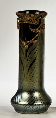 Loetz, 1900, STANGENVASE MIT METALLMONTIERUNG  Violettschwarzes Glas mit federblattartig gekämmter Fadenaufschmelzung in Silbergelb. Kräftig lüstriert. Florale Metallmontierung. H. 27