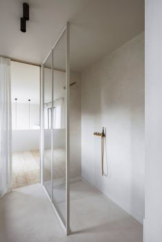 clever glass shower cubical with soft warm colour story.   Built-in wooden units and sheer, full-height curtains soften this otherwise stark apartment located in a converted brewery near Antwerp.