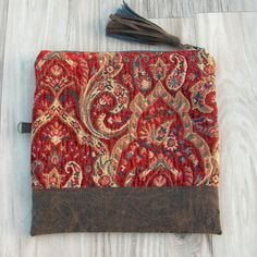 A simple folding clutch that will take you effortlessly from daytime into an evening out on the town. Its done in a richly textured red, blue and tan upholstery fabric with a sort of oriental rug pattern woven into it. I added a band of realistic brown aged faux leather around the bottom of the bag. These also make great luxe cosmetic bags    Ecofriendly bag features  * upholstery fabric with great texture  * handmade vegan leather tassel zipper pull charm * natural cotton lining…