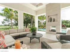 13881 Williston Way, Naples, FL 34119 | Outdoor living room with fireplace, overlooking the pool and golf course in Quail West - Naples Modern