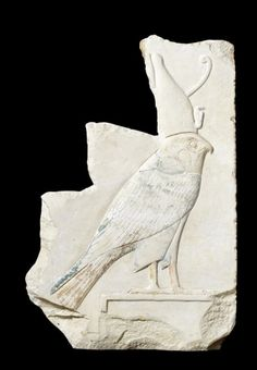 An Egyptian limestone relief of Horus  Early Middle Kingdom - early New Kingdom, 11th-18th Dynasty, circa 2133-1295 B.C. Sculpted in relief, depicting a Horus falcon in profile to the right, wearing the double crown, with a frontal uraeus, with finely carved anatomical details of the feathering, feet and face, the wings with added blue-green paint, the feet and tail in ochre, the falcon standing on a rectangular plinth