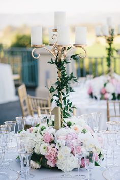 Our gold iron candelabra with lush flowers at the base (hydrangeas, garden roses, peonies, antique spray roses) with pretty Italian ruscus vine along the stem. It was so lovely when the sun went down! winecountryflowers.com