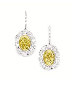 PAIR OF FANCY YELLOW DIAMOND AND DIAMOND PENDENT EARRINGS.  Each suspending on an oval fancy yellow diamond weighing 5.88 and 5.24 carats respectively, framed by oval diamonds, embellished by circular-cut diamonds extending to the hook surmount, the diamonds altogether weighing approximately 17.00 carats, mounted in platinum and 18 karat yellow gold.