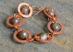 """Earth-tone agates wire wrapped inside of large copper washers and linked together. Approximately 7"""" in length with a handmade hook-and-eye clasp.                                                                                                                                                                                 More"""
