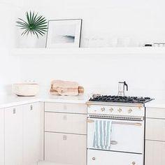 Chalé Paradisíaco com decoração clean, cozinha branca, cozinha com quadro, prateleira. fogão branco.