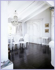 French Scandinavian White Dining - dark wood floor, white furniture, chandelier, architectural elements.