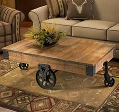 Hand-crafted, plank-style table with wheels has the look of an old cart, but is a useful, intriguing coffee table. Sturdily crafted of hardwoods with a distressed brown finish. Exposed metal hardware with a black powder coat.