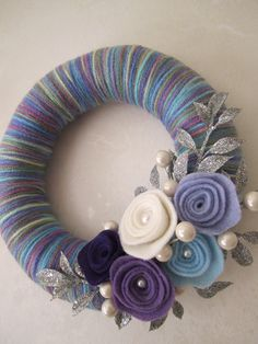 8 inch straw wreath wrapped in purple/ blue mixed color yarn, decorated with felt roses, pearls, and glitter silver leaves. No instructions, just ideas! Crafty Home Decor Diy Yarn Wreath, Crochet Wreath, Felt Flower Wreaths, Straw Wreath, Felt Wreath, Wreath Crafts, Felt Crafts, Yarn Wreaths, Crafts With Yarn