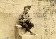 A war orphan wearing a US Army hat sits on a stone step and reads. Corbis. October 10, 1918.
