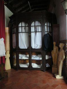 Mobiliário do século XVIII, em madeira escura recortada e trabalhada, com vidros nas portas, tecido branco cobrindo a visão do interior do móvel. Ex-votos de parafina medindo aproximadamente 1,50 mt.