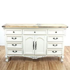 This country farmhouse dresser is featured in a solid wood with a distressed white paint finish and raw wood panel top. This long dresser has 9 drawers, 1 cabinet and carved floral leaf accents. Unique storage piece perfect as a buffet sideboard! #countryfarmhouse #dressers #longdresser #sandiegovintage #vintagefurniture