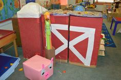 just 1 section of our farm theme farmers market / barnyard dramatic play. barn & silo and pig from cardboard boxes, pool noodle horses, raffia for hay.