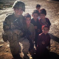 U.S. Infantryman takes a picture with hungry children in a taliban ruled area.