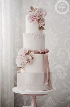 Featured Cake: Cotton & Crumbs; Romantic four tier white and pink wedding cake accented with flowers
