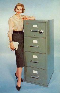 Woman enjoying alone time with filing cabinet. 1950s Office wear.