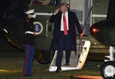 U.S. President Donald Trump salutes a U.S. Marine as he disembarks from Marine One on his return to the White House from a long weekend at…
