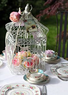 Tea:  A white wire birdcage with flowers makes an attractive centerpiece for this garden tea table.