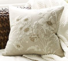 "Potterybarn.  Pale, textural poppies rendered in ivory embroidery with metallic beads and sequins have a neutral, tone-on-tone style in this cotton pillow cover.    18"" square   Hand embroidered.   Made of pure cotton.   Reverses to solid.   Button closure; insert sold separately.   Machine wash."