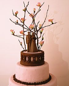 In Bermuda, couples top their wedding cakes with tiny saplings, which they plant to grow as their marriages do. Here, a milk-chocolate figurine, formed in a replica of a 1920s mold, stands on a faux top tier of Styrofoam coated to match the cake. The flowering quince branches above were painted with chocolate (choose pesticide-free foliage). Chocolate modeling dough makes a balustrade and miniature roses. The rolled fondant is tinted pink to pick up the hue of the quince.