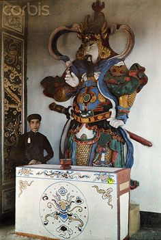 Annam, Vietnam --- A young mandarin stands beside an elaborately robed statue --- Image by © W.
