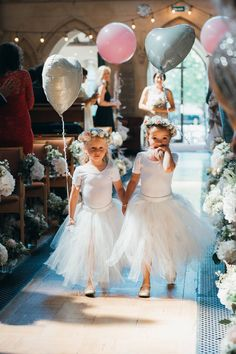 White ballet-inspired flower girl outfits with tutu skirts and heart balloons.