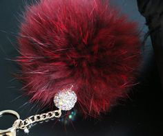 Burgundy, New Design  DESCRIPTION: Lend a touch of luxury to your favorite accessory with this elegant key chain and purse accessory. Its not just another pom-pom key chain. This lovely whimsical accessory features:  * Genuine Plush Rabbit Fur Pom-Pom in Burgundy with Black Tips , Hand-dyed * Genuine Swarovski Crystal Charm * Large AB Crystal Ball Accessory * Large Lobster Clasp, Metal Chain, Split Key Ring w/Swivel Connector * Pom-Pom measures approx. 5 - 6 inches in diameter, 12 - 13 cm…