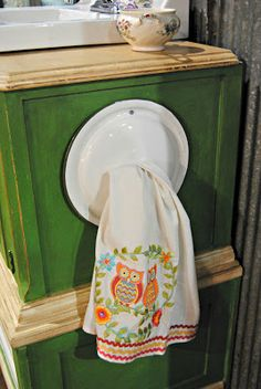Keep your hand towels organized by hanging them on the side of the vanity with something clever, like an enamelware pot lid!