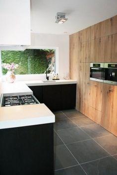 Modern kitchen with large wrap around window. Dark cabinets and raw wood.