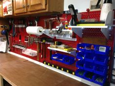 A well organized tool workbench with a Wall Control Master Workbench Kit. The red metal pegboards and white accessories with blue bins really make the space pop!