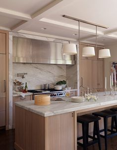 calcutta gold rift oak that is whitewashed not venner Architect William Hefner made a stainless-steel cover plate for the hood and framed the range area with Calacatta gold marble, to balance all the wood. Wolf 60-inch range.