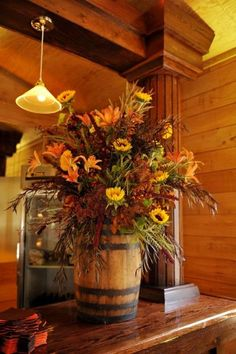Gorgeous array of fall flowers on display in an old wine barrel.
