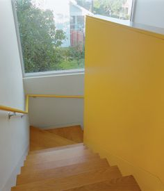 Bestor gave each area of the house its own color scheme. The bright yellow stairwell maintains a cheery mood throughout.  Photo by Ye Rin...