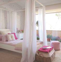 Domitorio infantil con un gran ventanal, papel pinado y cama con dosel
