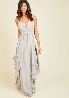 A softening of the music means it's your time to shine as belle of the ballroom in this grey gown! As you sway across the dance floor, the ruffled skirt of this open-back maxi accentuates the elegance of your movement. Complete with a plunging neckline, this dress was made for moments like this!