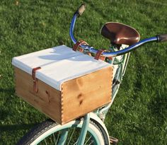 Get that European look and feel with this beautiful re-purposed wine crate bike basket with a Danish oil finish. It comes with a natural cotton canvas top to keep items in and has leather ties to hold the rolled up canvas back for larger items. The box attaches to the bike with 1-inch oiled leather straps, which provide a sturdy ride for you and the contents. Whether it's an outing in the wine country or just a run to the store, this is a very sturdy and well made classic carrier.  Please…