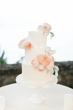 Three tier peach rose topped wedding cake: http://www.stylemepretty.com/2016/11/14/an-epic-wedding-ceremony-set-cliffside/ Photography: Jessica Kay - http://www.jessicakay.com/